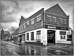 You can`t get wetter than a Kwik-Fit Fotter! (Jason 87030) Tags: kwikfit mot gargae service tyres exhaust repairs building ghost architecture lawford road uk midlands warks warwickshire wiundows bay history shot frame border bw bbw black white noir blanc blackandwhite rain water reflections puddles rugby town auto