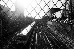 ANALOG; Ilford PAN 100 (ewitsoe) Tags: 24mm analog analogue city cityscape ilfordpan100 nikonfm2 street warszawa winter erikwitsoe erikwitsoecom film urban warsaw gate wire train sunset monochrome mono bnw blackandwhite grain travel fence chickenwire dof tracks trainstation