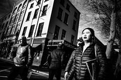 42nd Parallel (Kieron Ellis) Tags: woman man people walking crossing road bright tree wall windows bicycle 42 sky cloud candid street blackandwhite blackwhite monochrome
