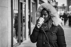 Coffee, To Go (Leanne Boulton) Tags: urban street candid portrait portraiture streetphotography candidstreetphotography candidportrait streetportrait eyecontact candideyecontact streetlife woman female girl face eyes expression mood emotion feeling fur furry fluffy hood drinking coffee spring scarf tone texture detail depthoffield bokeh naturallight outdoor light shade city scene human life living humanity society culture lifestyle people canon canon5dmkiii 70mm ef2470mmf28liiusm black white blackwhite bw mono blackandwhite monochrome glasgow scotland uk
