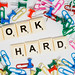 Work hard text with colorful pins and clips on white surface