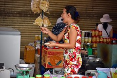"""Paring Produce and Pointing:  Happy Vendor, """"And my next point is...."""" (Ginger H Robinson) Tags: paring knife freshproduce pointing laughing animated happy vendor early morning benthanhmarket biggest oldest landmark market saigondistrict1 saigon hcmc vietnam southestasia bandaid"""
