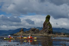 Paddlers in sea kayaks enjoy the calm waters near the sea stack, the 'Green Head' (daniellacy562) Tags: adventure boats britishcolumbia bunsbyislands calm clouds editorialcontent greenhead islets kayaktrip landscape leisure mountains outdoors outside pacificnorthwest pacificocean paddling people recreation reef rockyshore sea seakayaks seastack summer travel vacation vancouverisland water westcoast