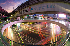Pathumwan intersection (Bangkok- City of Life) - the traffic light trails of vehicle below the skywalk above the famous intersection in the heart of Bangkok at dawn. (baddoguy) Tags: above advertisement bangkok below built structure capital cities circle city street cityscape color image copy space curve dawn diminishing perspective elevated walkway fire natural phenomenon high angle view horizontal igniting journey land vehicle lifestyles light trail lighting equipment line art low modern multi colored no people outdoors photography placard point rail transportation railroad track road intersection siam square sky sunrise thailand traffic train travel destinations twilight urban