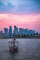 Doha Bay (IRRphotography) Tags: doha qatar gulf persian middleeast travel boat water baywestbay city skyscrapers buildings flag sunset clouds sky
