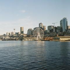Seattle waterfront (sailronin) Tags: seattle waterfront ferrycrossing spaceneedle bigwheel docks bay harbor water elliottbay downtown cranes film analog rollei rolleiflex6008 carlzeiss zeissplanar80mm kodakfilm ektar100 colorfilm 120rollfilm