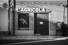 L'Agricola (Laura Sergiampietri) Tags: bn urban bw blackwhite biancoenero shadows sunlight availablelight naturallight building concrete street vintage sign lagricola smcpentaxda1770mmf4alifsdm smcpda1770mmf4alifsdm shop shutters façade