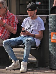 IMG_1269 (Skinny Guy Lover) Tags: outdoor people candid guy man male dude sitting sit seated cap smartphonezombie jeans bluejeans sneakers earpods earbuds earplugs shortbeard rippedjeans tornjeans
