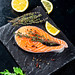 Fresh salmon steak on a black stone tray with spices and lemon slices