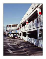 Along the Lot (Thomas Listl) Tags: thomaslistl color 35mm parkinglot garage mainstation topography red sky blue vanishingpoint lines geometry architecture würzburg