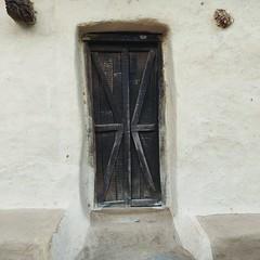 Modest Ingenuity. (Gattam Pattam) Tags: wall architecture houses village chhattisgarh india rural blue street door entrance walk mud earth threshold black white