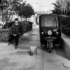 On each side (Go-tea 郭天) Tags: qingdao shandong républiquepopulairedechine cn sidewalk motorbike motorcycle parked side left right balance lines path middle woman alone lonely walk walking young cold winter sun sunny shadow symmetric lady glasses portrait street urban city outside outdoor people candid bw bnw black white blackwhite blackandwhite monochrome naturallight natural light asia asian china chinese canon eos 100d 24mm prime