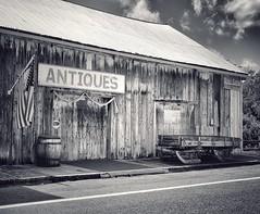 Antiques (podolux) Tags: 2012 nikon nikondx dx d5100 nikond5100 antiques antiquestore oneword onewordantiques blancoynegro blackandwhite bw building postprocessing snapseed sign signs