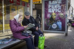 Feeling Epic (Leanne Boulton) Tags: urban street candid streetphotography candidstreetphotography streetlife portrait portraiture candidportrait streetportrait wideangle man woman male female couple face faces expression posture mood atmosphere bodylanguage communication interaction bench busstop public transport poster juxtaposition complimentarycolour purple yellow cap scarf old elderly perspective tone texture detail depthoffield bokeh naturallight outdoor light shade city scene human life living humanity society culture lifestyle people canon canon5dmkiii 35mm ef2470mmf28liiusm color colour glasgow scotland uk leanneboulton