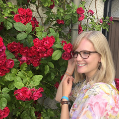 A Young Blonde Woman With Glasses Smiling in Front of a Wall Full of Colorful Red Flowers (Jonatan Svensson Glad (Josve05a)) Tags: cute happy smiling people smile attractive happiness women girls face person portrait adult human pretty cheerful leisure hair joy summer day outdoors plant dress glasses blonde park outdoor spring enjoyment flowers floral botany outside sweden blond flower squareimage 19years gotland visby takenonmobiledevice vascularplant