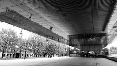 Lentos Kunstmuseum Linz (halifaxlight) Tags: austria linz riverdanube lentoskunstmuseumlinz museum architecture entry plaza street trees pedestrians reflections church bw