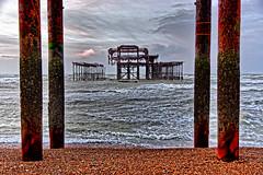 Framed (Geoff Henson) Tags: ruin wreck abandoned rust deserted pier pillars beach pebbles stones sea ocean water waves breakers sky cloud morning brighton sussex