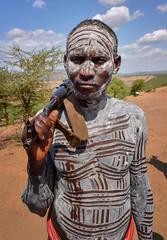 Karo Warrior (Rod Waddington) Tags: africa african afrique afrika äthiopien ethiopia ethiopian ethnic etiopia ethnicity ethiopie etiopian omovalley outdoor omo omoriver karo tribe traditional tribal ak47 gun rifle weapon portrait people painted landscape village man warrior