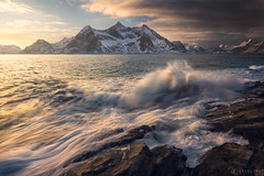 Wake up call (Ron Jansen - EyeSeeLight Photography) Tags: norway lofoten nordland winter morning sunrise wave splash sea ocean waves light glow gold golden mood dark mountain snow water cloud clouds