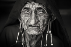 India, old Rabari woman (Dietmar Temps) Tags: asia bhuj blackandwhite camel camelherder cattle desert earrings eyes face greatrannofkutch gujarat india nomadictribe oldlady portrait rabari sand shepard thardesert travel tribalwoman woman wrinkles 50mm
