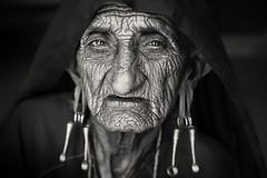 India, old Rabari woman (Dietmar Temps) Tags: asia bhuj blackandwhite camel camelherder cattle desert earrings eyes face greatrannofkutch gujarat india nomadictribe oldlady portrait rabari sand shepard thardesert travel tribalwoman woman wrinkles 50mm