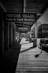 Lonely Shopkeeper (Rohit KC Photography) Tags: streetphotography blackandwhite alone waiting contrast shadows bw street travel canon canon5dmarkii mood outside shops photography fun hobby black white cars parking meter signs california sacramento oldsac dslr
