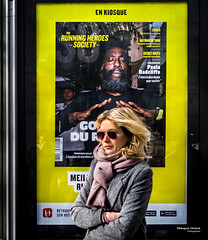Street - Laying-on of hands (François Escriva) Tags: street streetphotography paris france people candid olympus omd photo rue woman colors sidewalk newsstand newspapers kiosk poster ad billboard fun funny hakim tafari yellow black white sunglasses running heroes society