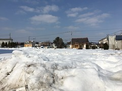 Snowy Field to the Buddhist Temple (sjrankin) Tags: 4march2019 edited kitahiroshima hokkaido japan snow weather clouds road buildings field buddhisttemple sky houses