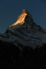 Matterhorn (Zermatt, Switzerland) - golden sunlight touching the tip of Matterhorn. (baddoguy) Tags: above abstract alpenglow autumn leaf color beauty in nature below blue clear sky cold temperature image copy space dawn europe european alps famous place focus on foreground gold colored horned international landmark landscape scenery local matterhorn national no people outdoors photography pinnacle peak pyramid shape scenics silhouette snow snowcapped mountain sunlight swiss switzerland tip touching tourism town travel destinations valais canton vertical village zermatt