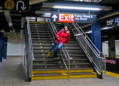 Urban Playground - Fulton Street Subway Platform, NYC (TravelsWithDan) Tags: youngwoman stairway sliding bannister goingthefastway city urban underground metro subway platform candid streetphotography red nyc newyork night canong3