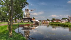 Flour Mill De Hoop, Bunschoten Spakenburg, Netherlands - 2681 (HereIsTom) Tags: webshots travel europe netherlands holland dutch view nederland views you nature sun tourists cycle vakantie fietsvakantie cycling holiday bike bicycle fietsen plus apple ios camera iphone 8 green 2008 bunschoten korenmolen spakenburg koren town dorp water tower mill de hoop ijsselmeer windmill houses buildings trees church molen village reflections 17 july 2014 juli stadsgracht gracht canal