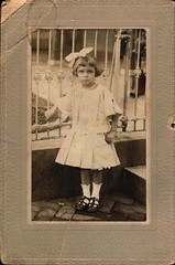 Frowning Girl (Familypapers) Tags: portrait blackandwhitephoto children babypictures younggirl frown child hairribbon dress fancy ironfence rotiron 5yearold streetscene pearlnecklace brick bricksidewalk