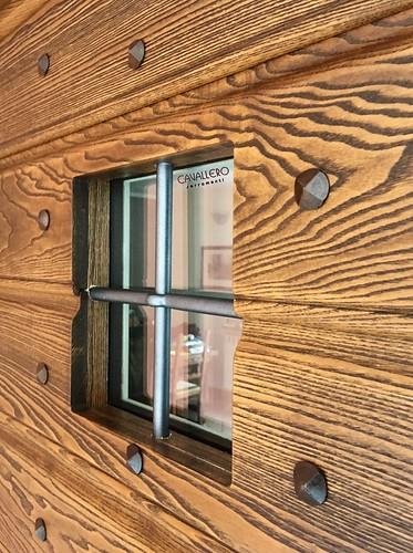 Dettaglio finestrella in portone in legno a doghe in Frassino