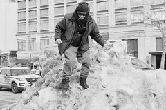 man on a snowbank (susanjanegolding) Tags: upperwestside manhattan smoking coat climbing winter snow hat headphones climb newyorkcity cold snowpile man weather sunglasses cigarette xpro2 xf35mmf2