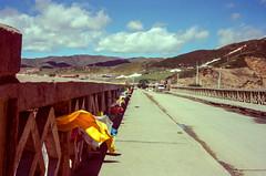 Prayer Flags on the Bridge (hiphopmilk) Tags: copyright©jaredyehwooehmoehfilms konica offroad 現場監督 zoom 35mm 135film film analog analogue jaredyeh hiphopmilk kodak travel china sichuan aba hongyuan tibetan qiongxi prayerflags bridge hill sky cloud
