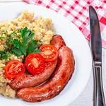 Funny lunch with porridge, sausages, tomatoes and herbs thumbnail