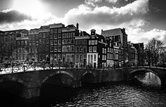 The City With A Proper Spring #6 (gorelin) Tags: shadow sunray woman man dog bike bicycle people spring flare water canal bridge sky sunrise sun streetshot stretshooting street city netherlands amsterdam white black blackandwhite blackwhite 28mm fe28f20 sonyilce7m2 ilce7m2 alpha sony 6