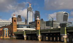 Cannon Street railway station and bridge, 1866, and skyscrapers in City of London. (edk7) Tags: olympusomdem5 edk7 2015 uk england london riverthames cityoflondon cannonstreet londoncannonstreetrailwayterminusopened1866 cannonstreetrailwaybridgebuilt1866renovated1886–1982 gradeiilisted dome train architecture building oldstructure city cityscape skyline urban office steel glass tower trainstation riverbank pier girder cloud sky crane construction