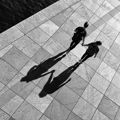 Hand in Hand (Leipzig_trifft_Wien) Tags: street streetphoto streetphotography shadopw light lightandshadow silhouette people human person walking abstract square diagonal pattern lines