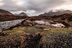 Isle of Skye [ Explore ] (NikNak Allen) Tags: scotland skye isleofskye island river water smooth rocks stones shingle reflection landscape view vista look mountain mountains cloud clouds sky snow capped low pov longexposure light shadow moody storm stormy