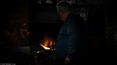 Strike while the iron is hot. (Neil. Moralee) Tags: branscombeforgeneilmoralee neilmoralee daek colour blacksmith smith smithy forge work iron ironworks fire man devon branscombe heat skill trade craft craftsman dark neil moralee olympus omd em5 hammer historic uk britain
