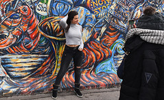 Pose By The Wall (Anthony Mark Images) Tags: posingbythewall cellphonephotography art wallmural painting streetart candid berlin berlinwall berlinermauer germany deutschland europe eastsidegallery outdoorgallery formereastberlin friends people portrait girls female prettygirl jeans greysweater darkhair earrings scarf hat blackwintercoat nikon d850 flickrclickx