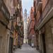 Kleine Gasse zwischen mediterranen Fassaden mit Blick auf die gotische Kirche