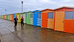 Runners (Croydon Clicker) Tags: beachhuts colours doors windows lamp promenade footpath pathway wet sky cloud women runners joggers people seaford sussex eastsussex huts sheds