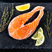 Raw salmon fillets on dark background