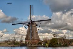A windmill in Kinderdijk (Roland B43) Tags: kinderdijk netherlands windmill water canal clouds takumar50mm14
