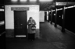 a presence (gguillaumee) Tags: film analog grain leicam7 leica bw blackandwhite metro undergound subway nyc newyork plartform upperwestside gotham woman lady reading alone lonely cadid street streephotography atmosphere introspection absorbed