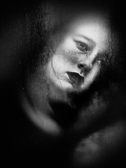 A woman looking through a window (Bill Eiffert) Tags: woman looking wimdow wet dark sad melancholy emotiona sadness blackandwhite nik