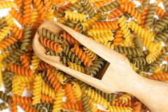 Pile of colorful macaroni with wooden spatula on the top (wuestenigel) Tags: dry color mediterranean background dinner red carbohydrate uncooked italian cook pile meal yellow white raw market whole closeup cooking focus macaroni healthy diet studio gourmet food fusilli ingredient wheat cuisine heap lunch macro green fresh tasty pasta staple