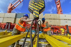 Sailors attach cables to a crane at the Kilo Pier at Naval Base Guam.